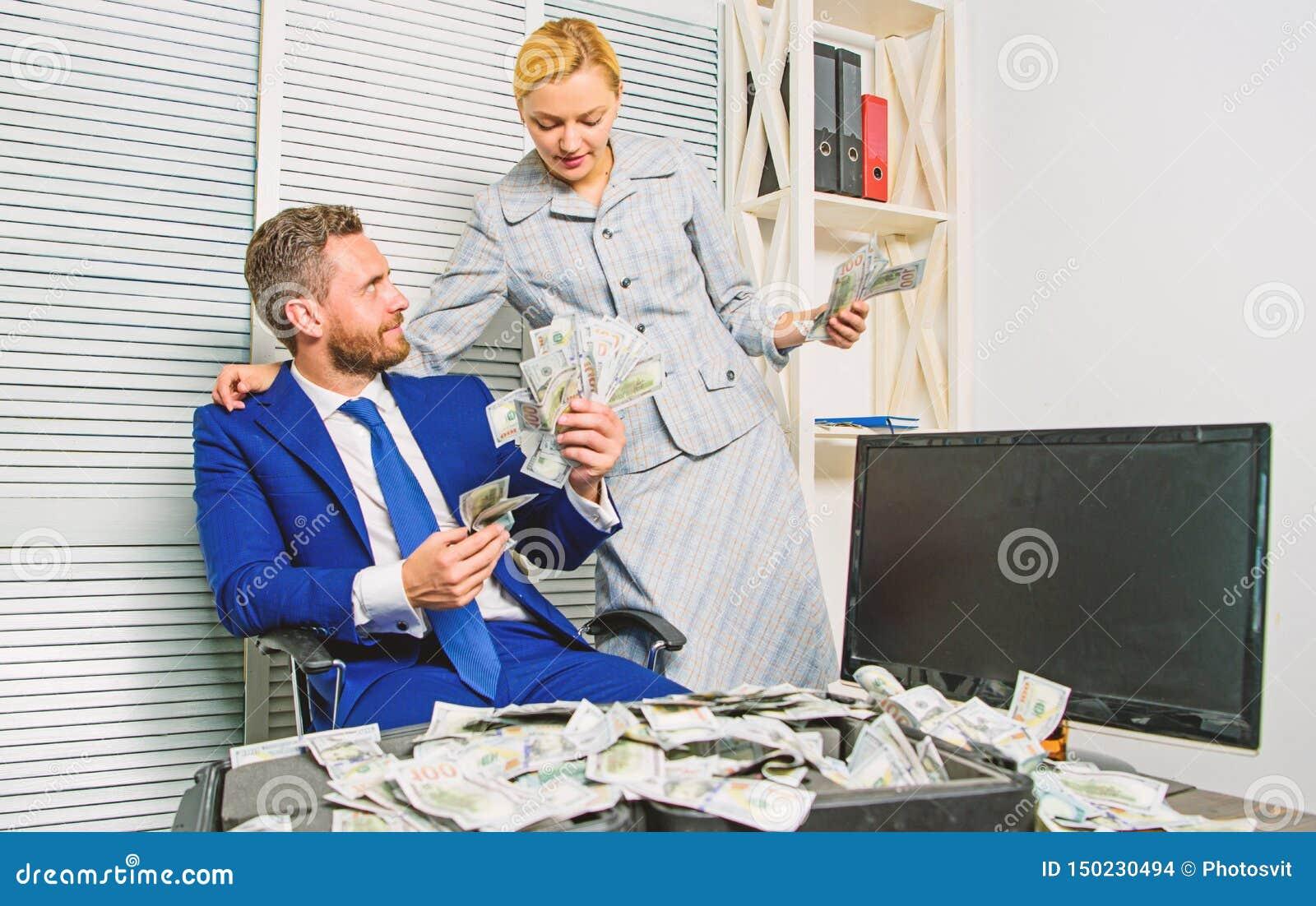 Contando o lucro do dinheiro Homem de neg?cios do homem e secret?rio da mulher com as c?dulas do d?lar da pilha Conceito do lucro