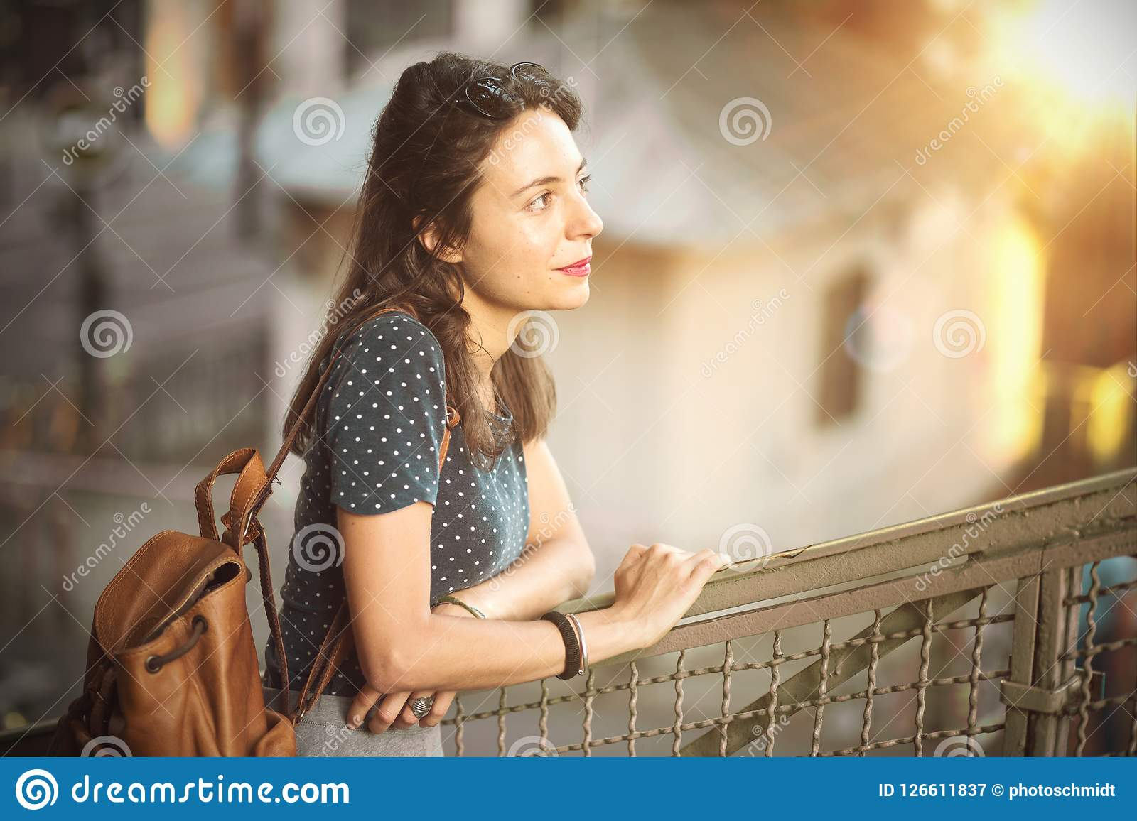 Contemplative young woman leaning on a banister