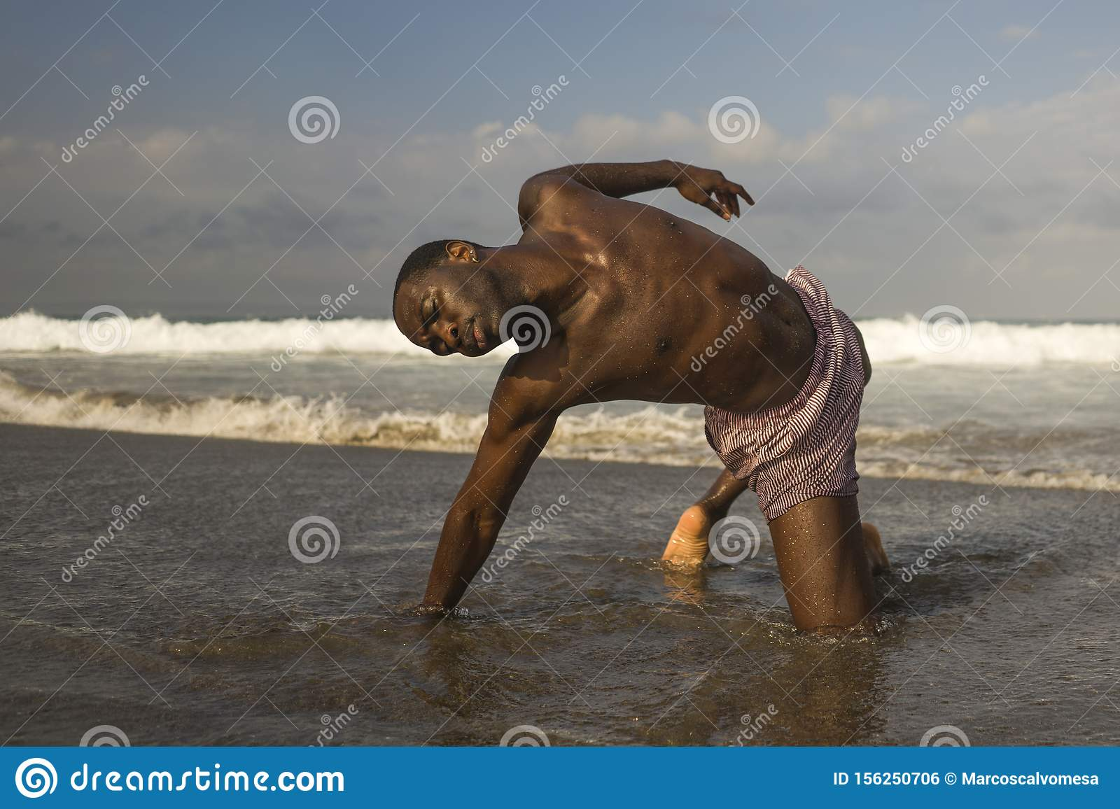 Contemporary dance choreographer and dancer doing ballet beach workout . a young attractive and athletic black African American