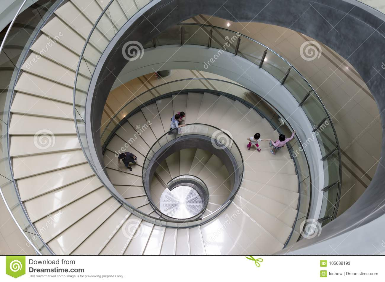 Unidentified Pedestrians Walking On Unique Modern Spiral Staircase