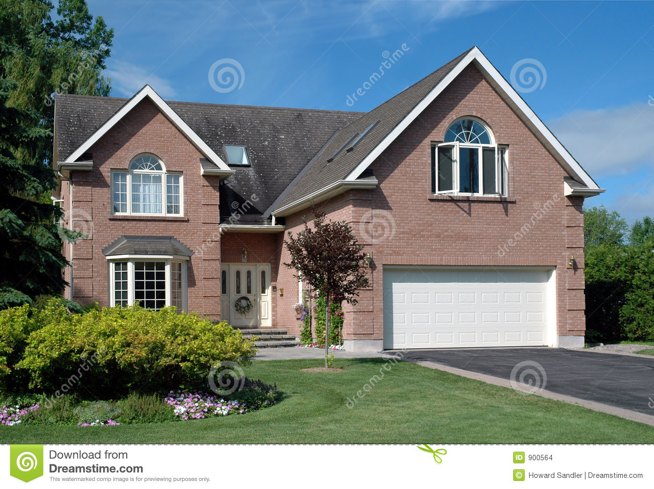 Large brick suburban house with attached garage and manicured lawn.