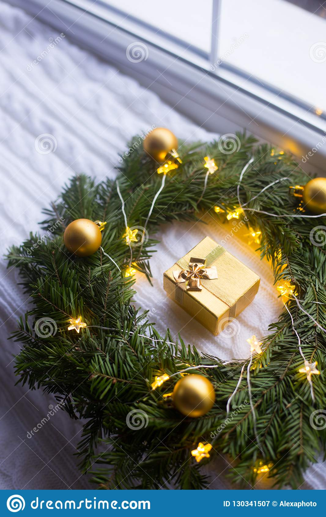 Contenitore di regalo dorato vicino alla corona dell abete decorata con le palle di Natale ed arrotolata con la ghirlanda d ardor