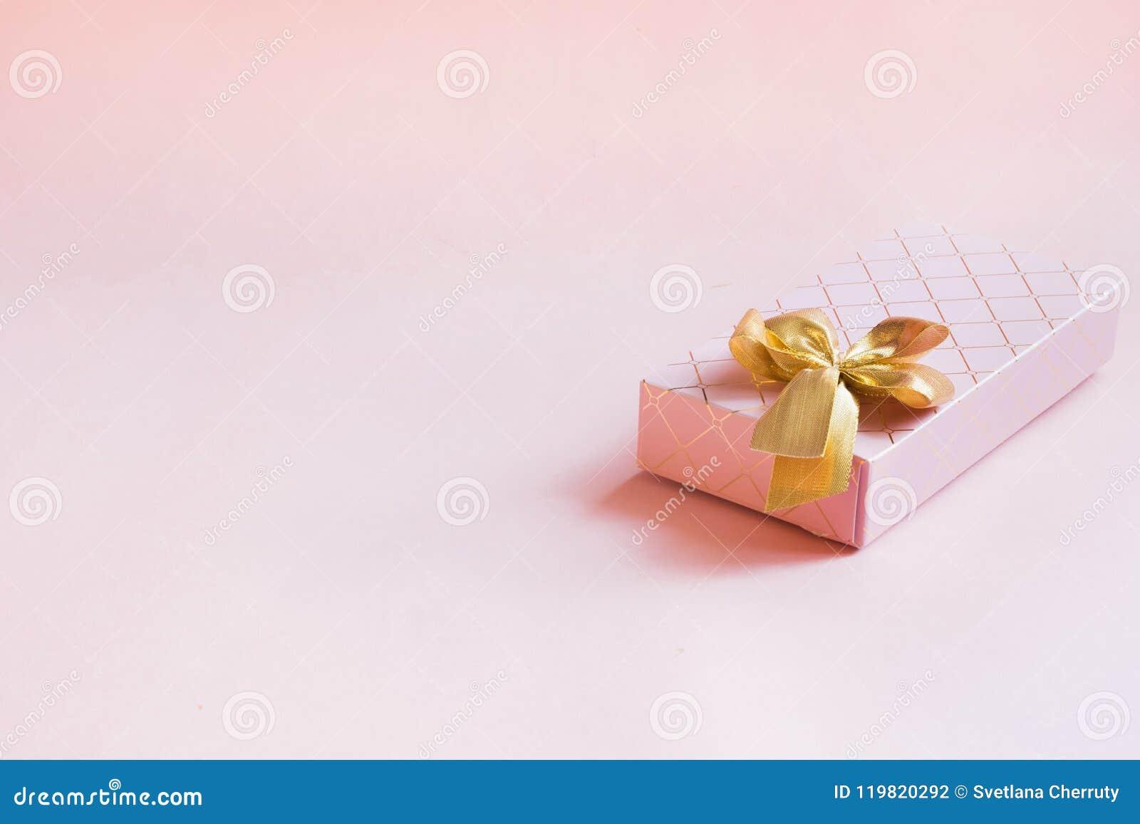 Contenitore di regalo femminile con il nastro dorato sul rosa pastello punchy Compleanno Copi lo spazio
