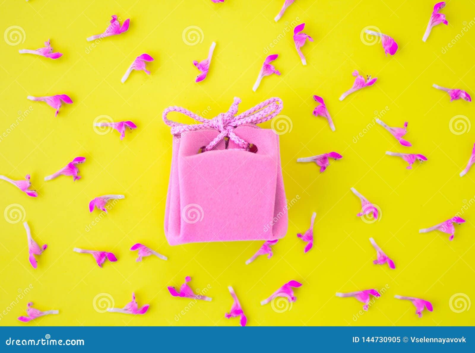 Contenitore di regalo rosa su un fondo giallo con i fiori Concetto festivo Disposizione piana, vista superiore
