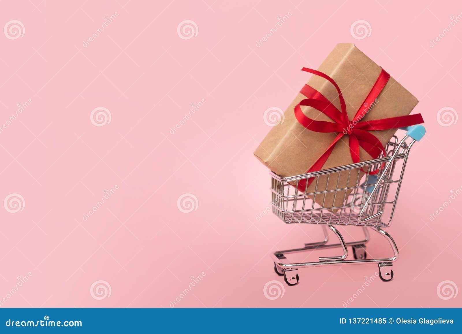 Contenitore di regalo in un carrello su fondo rosa Concetto per gli acquisti Copi lo spazio