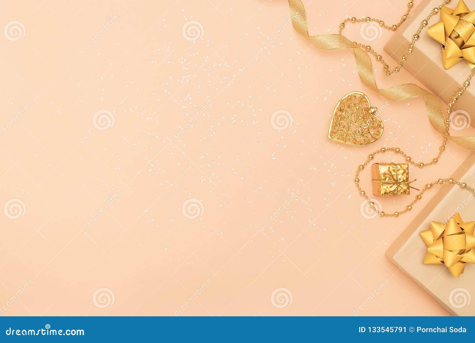 Contenitori di regali o scatole dei presente con gli archi, la stella e la palla dorati su fondo dorato per cerimonia di complean