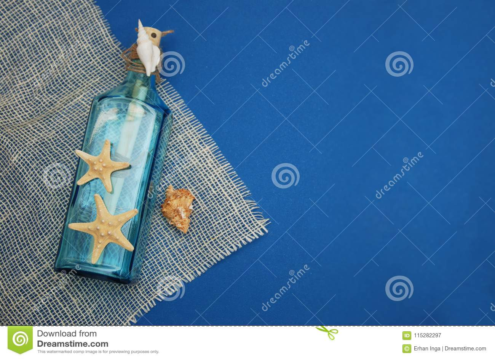 Contexto náutico do tema, garrafa decorativa com shell, estrela do mar no fundo do azul de Depp Copie o espaço Foco seletivo