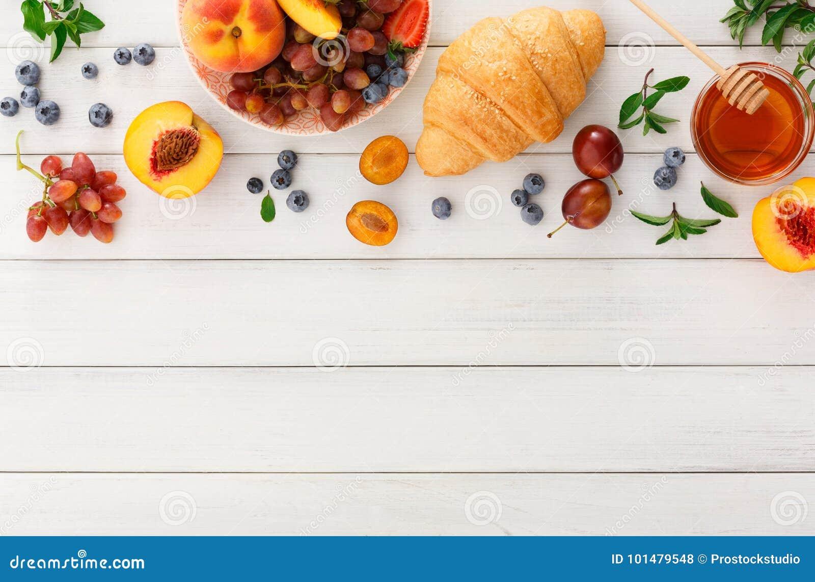 Continentaal ontbijt met croissants en bessen op wit hout