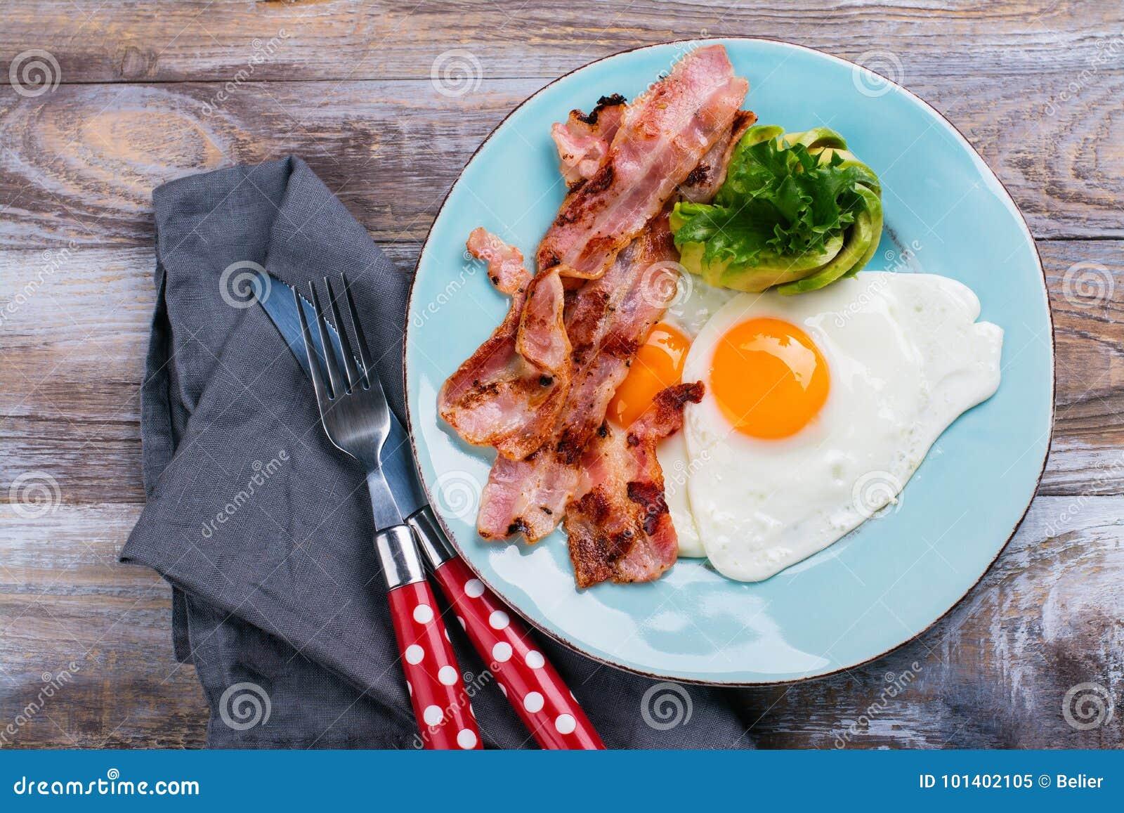 Continentaal ontbijt met gebraden eieren, bacon en avokado