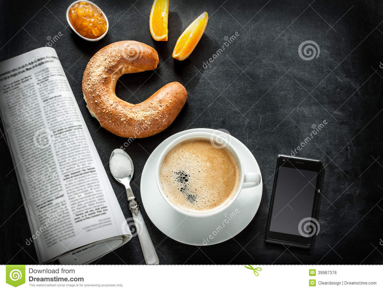 Continental breakfast and mobile phone on black chalkboard