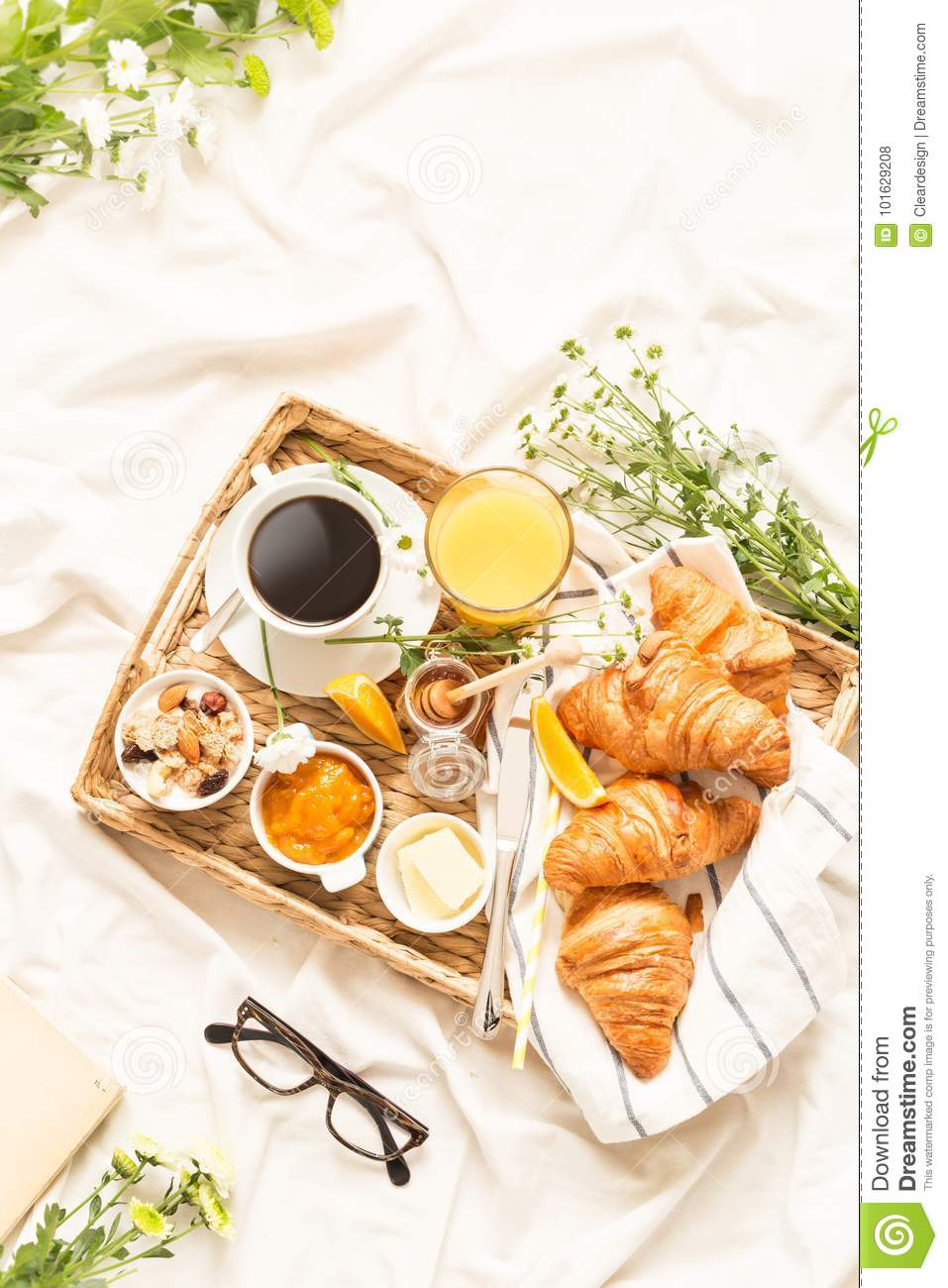 Continental breakfast on white bed sheets - flat lay