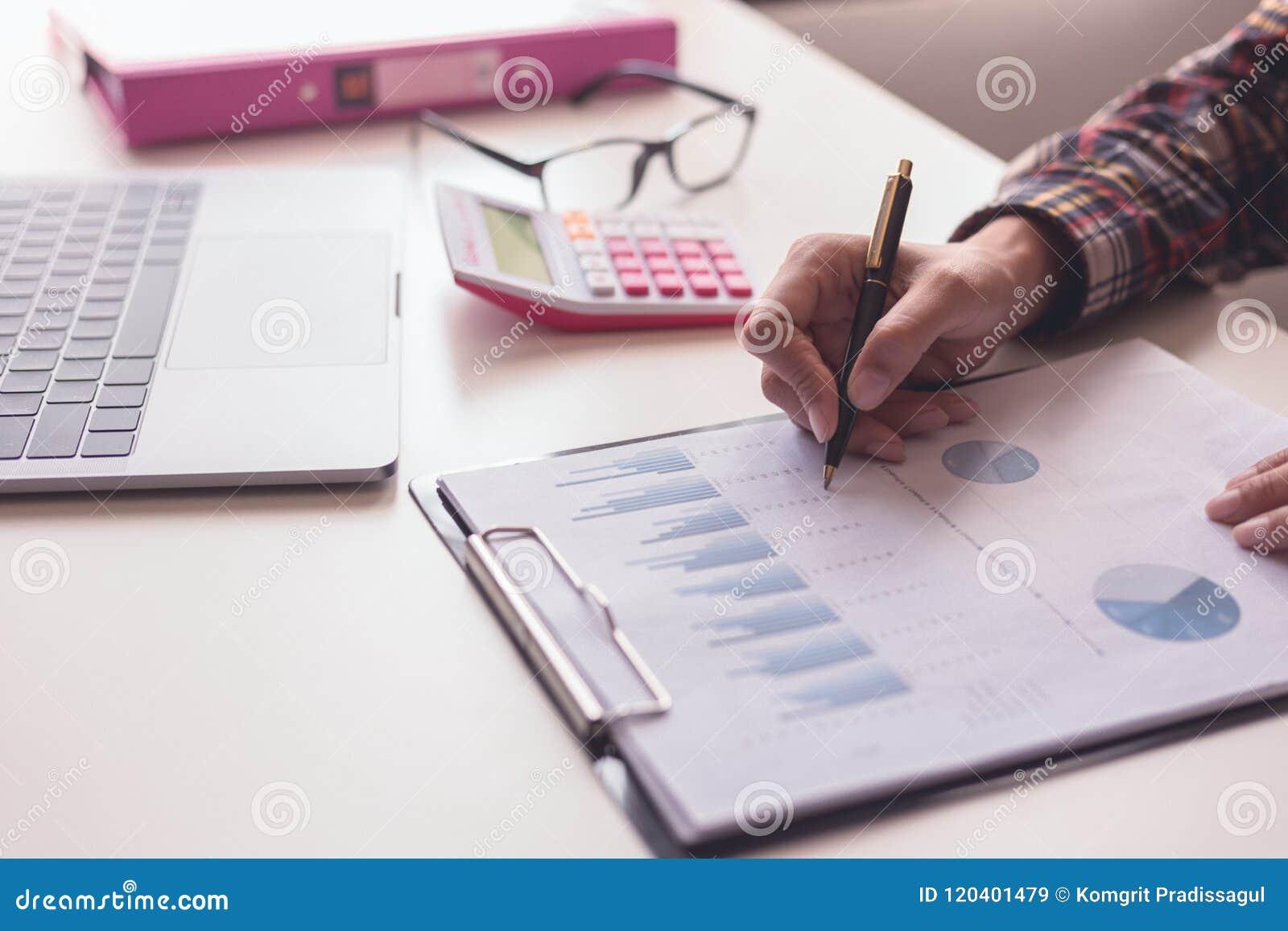 Contrôle d homme d affaires au sujet de coût et de faire le rapport de graphique de finances au bureau