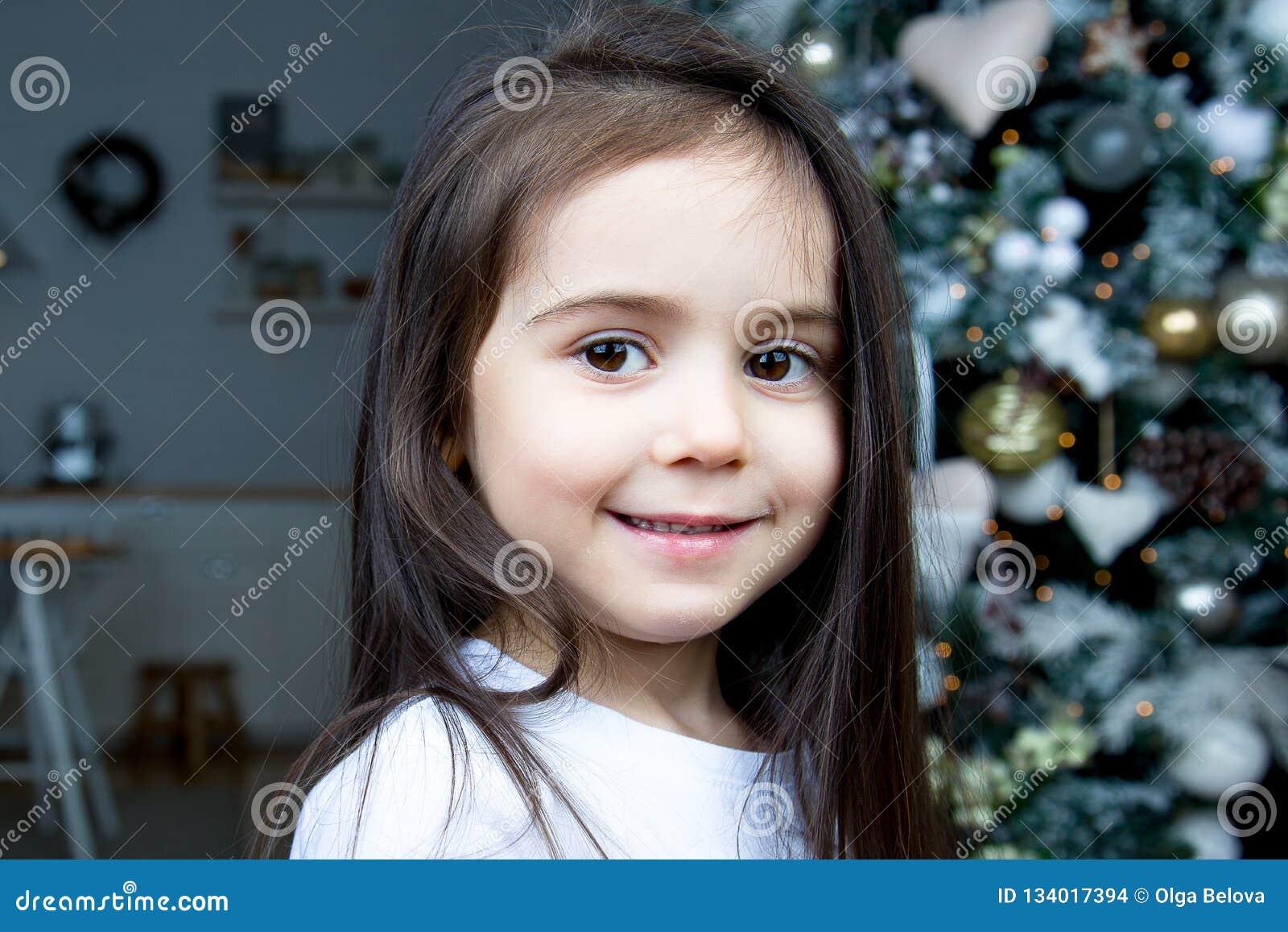 Contra el árbol de navidad, un retrato de una niña