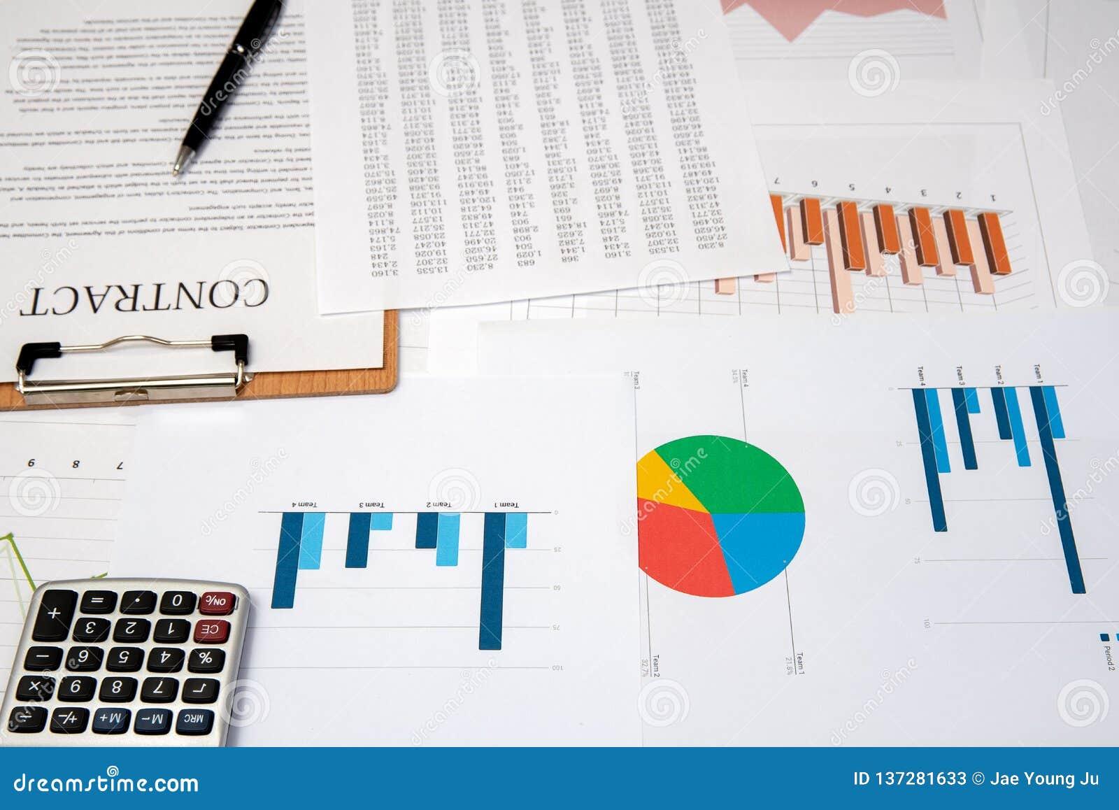 Contracten, grafieken, en grafieken op het bureau bedrijfsbureauconcept