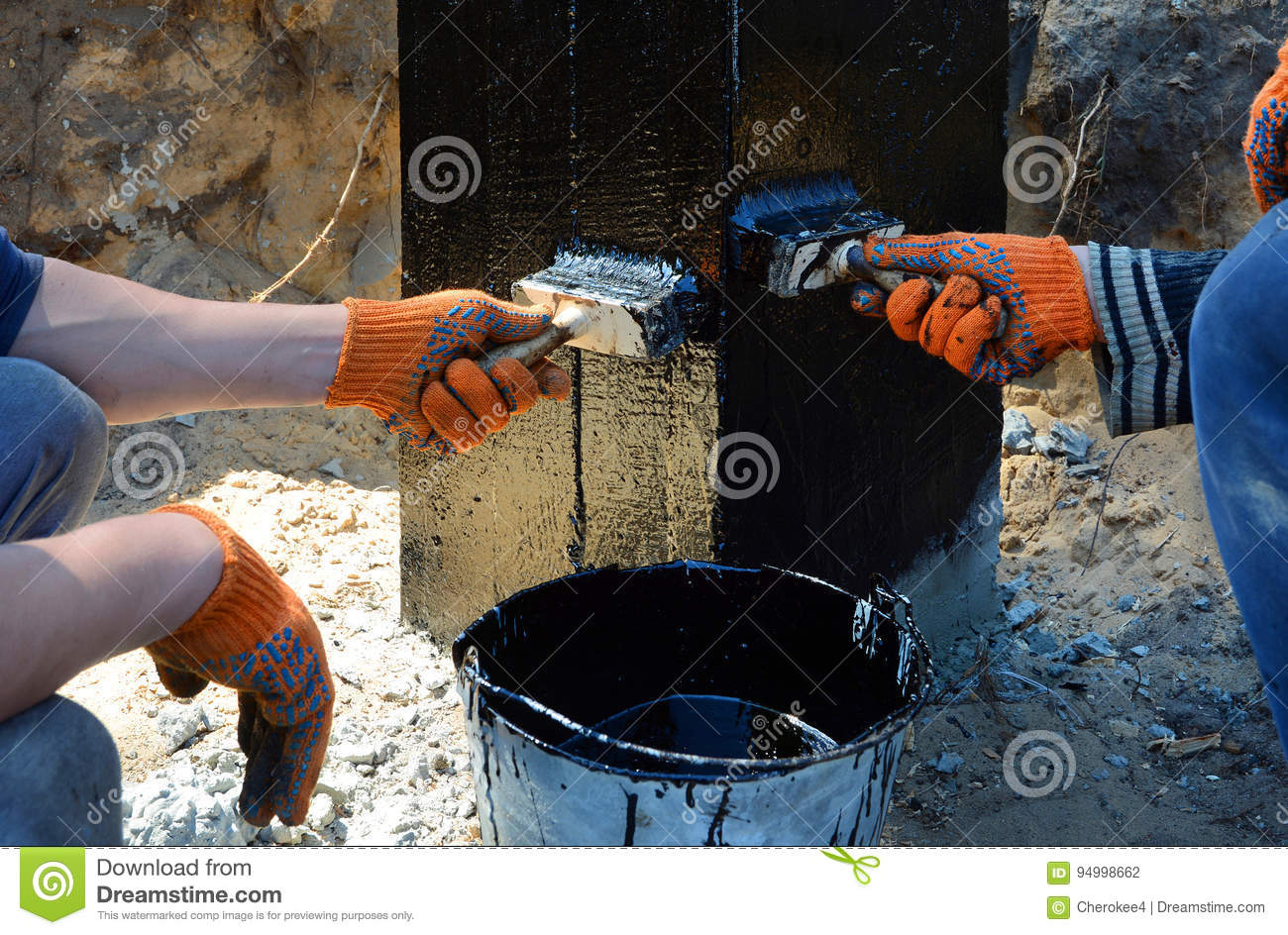 contractor painting black coal tar or bitumen at concrete surface by