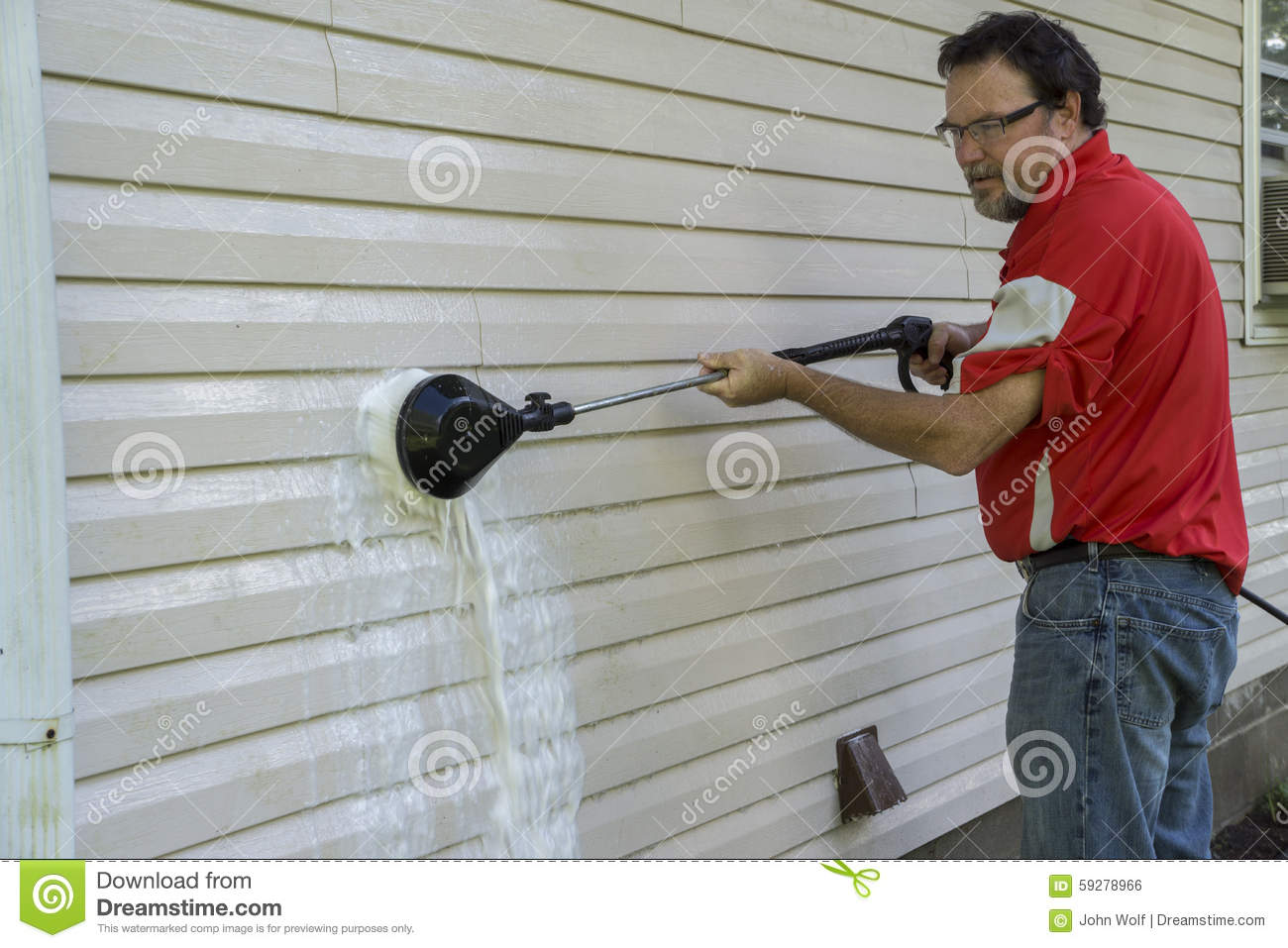 Contractor Using A High Pressure Brush To Remove Algae And