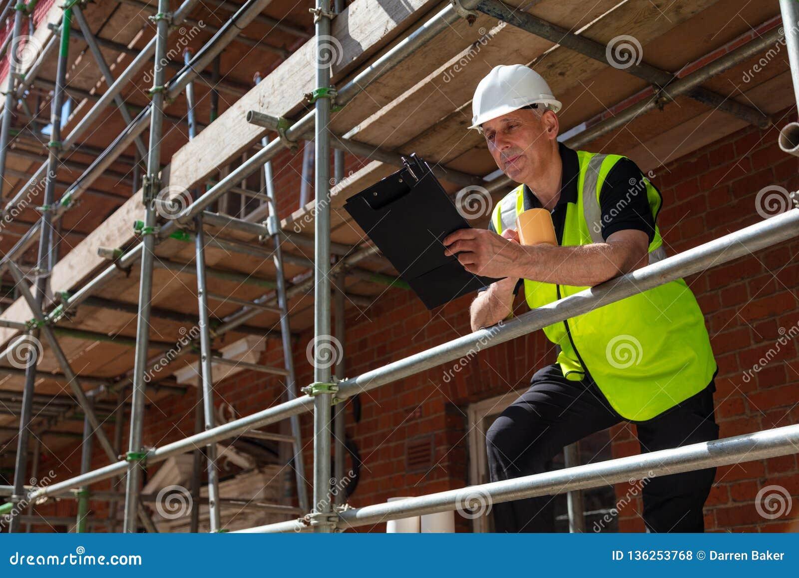 Contramestre Builder da construção no terreno de construção com prancheta