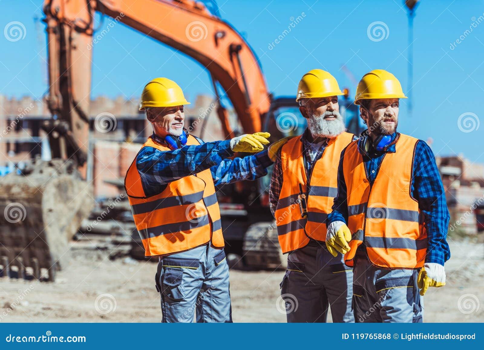 Contramestre que mostra a construtores algo no canteiro de obras apontando o seu