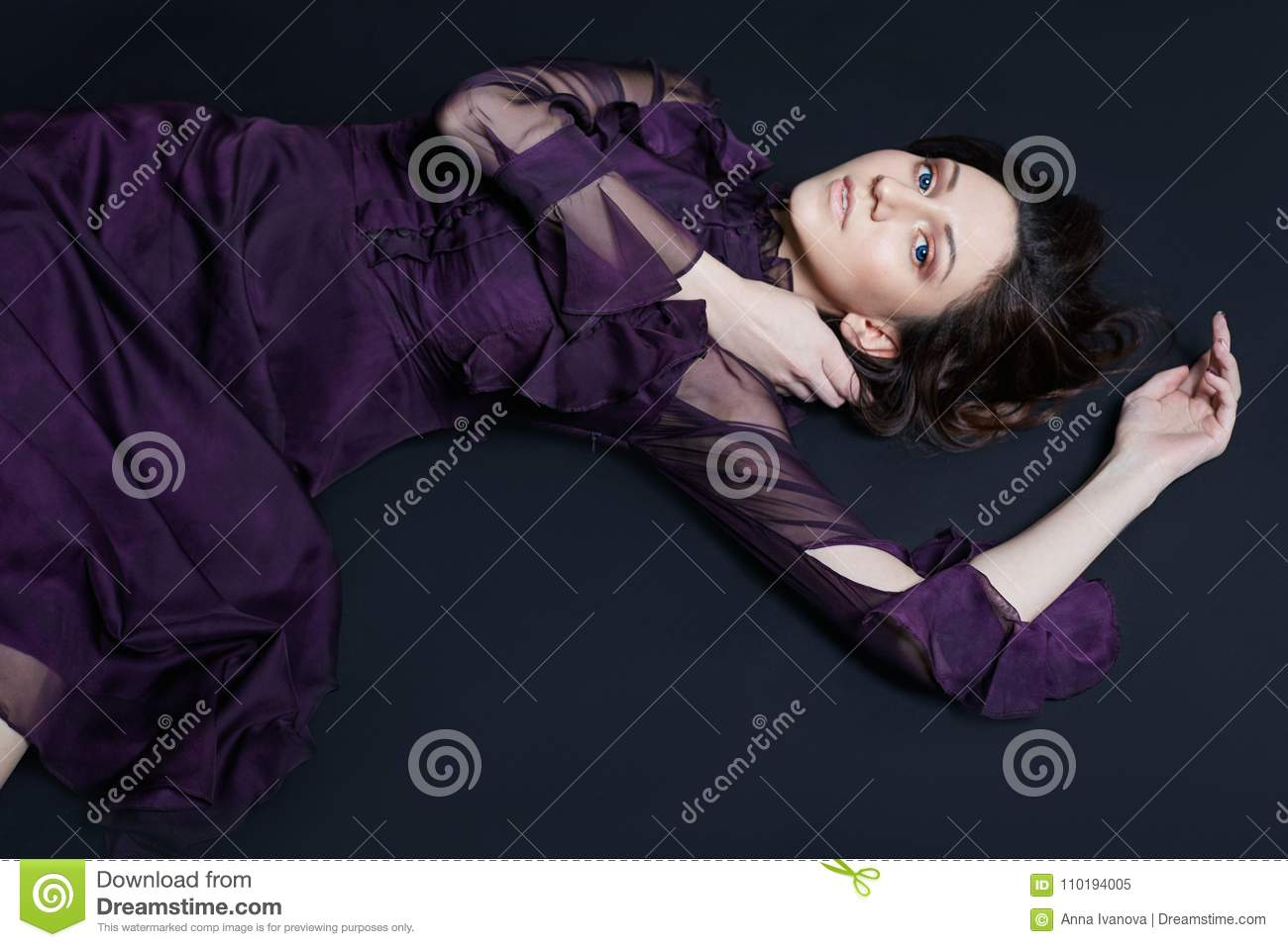 Contrast fashion Armenian woman portrait with big blue eyes lying on the floor in a purple dress. Lovely gorgeous girl posing