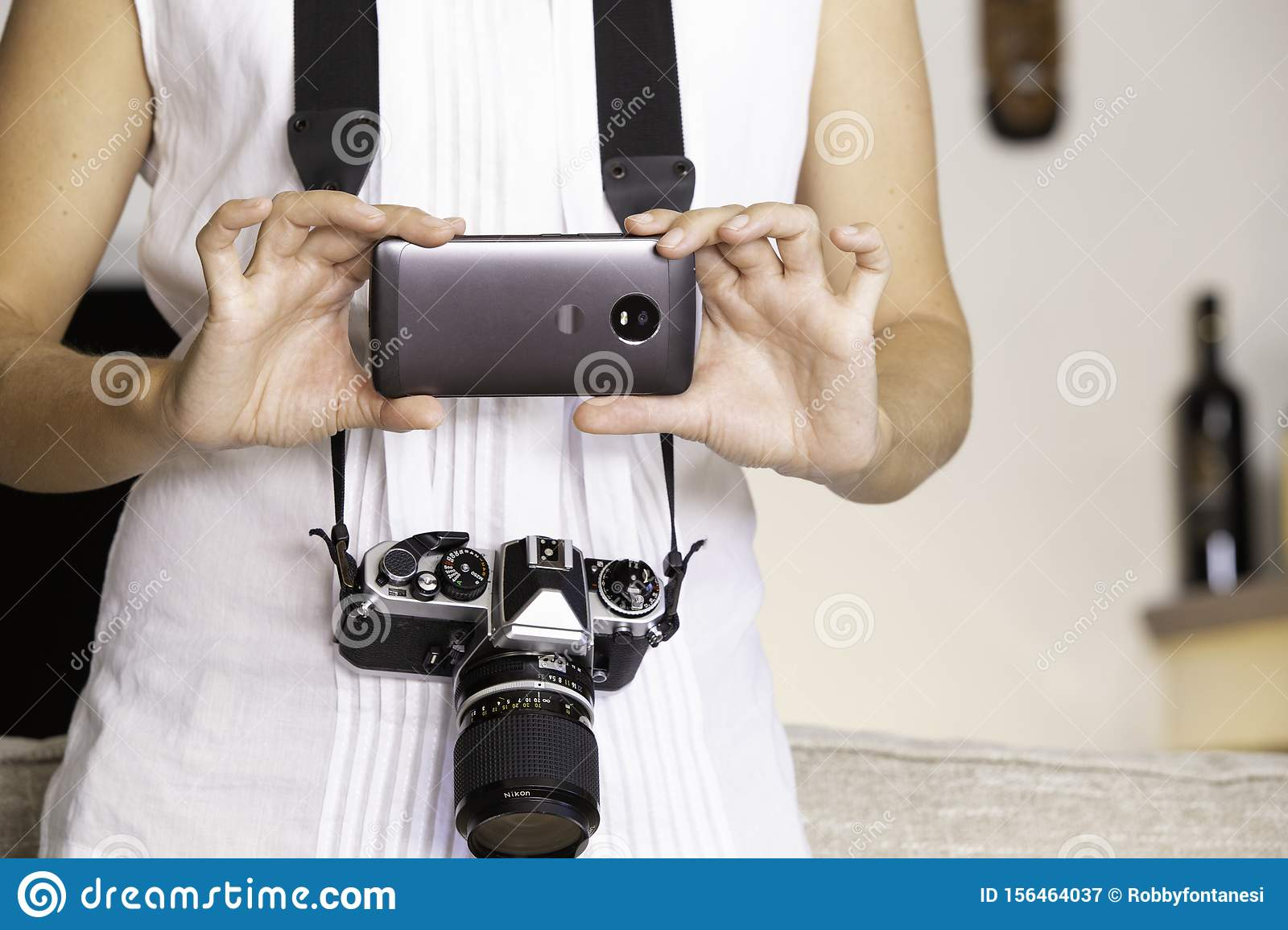 Contrast between old and modern times: a young woman with a vintage camera around her neck fiddles with her smartphone