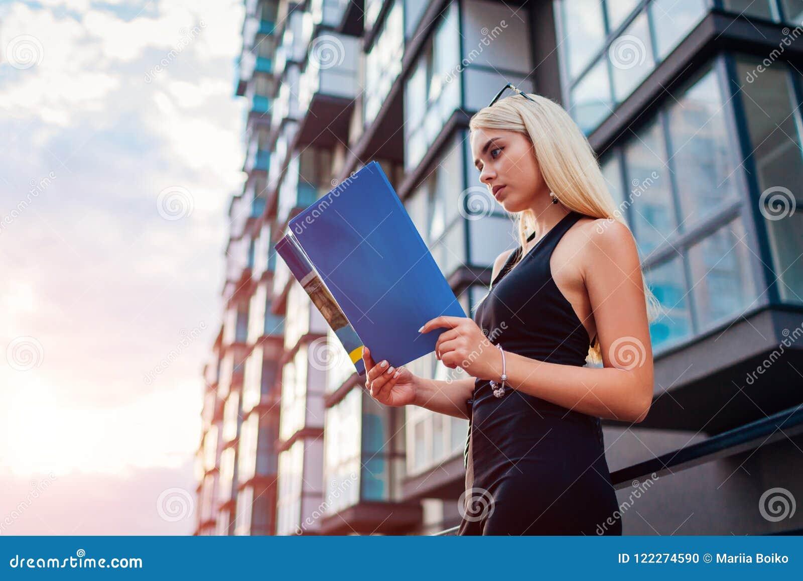 Contrato real louro novo da leitura do agente do eastate pela construção moderna do multi-andar na cidade A mulher de negócios ex