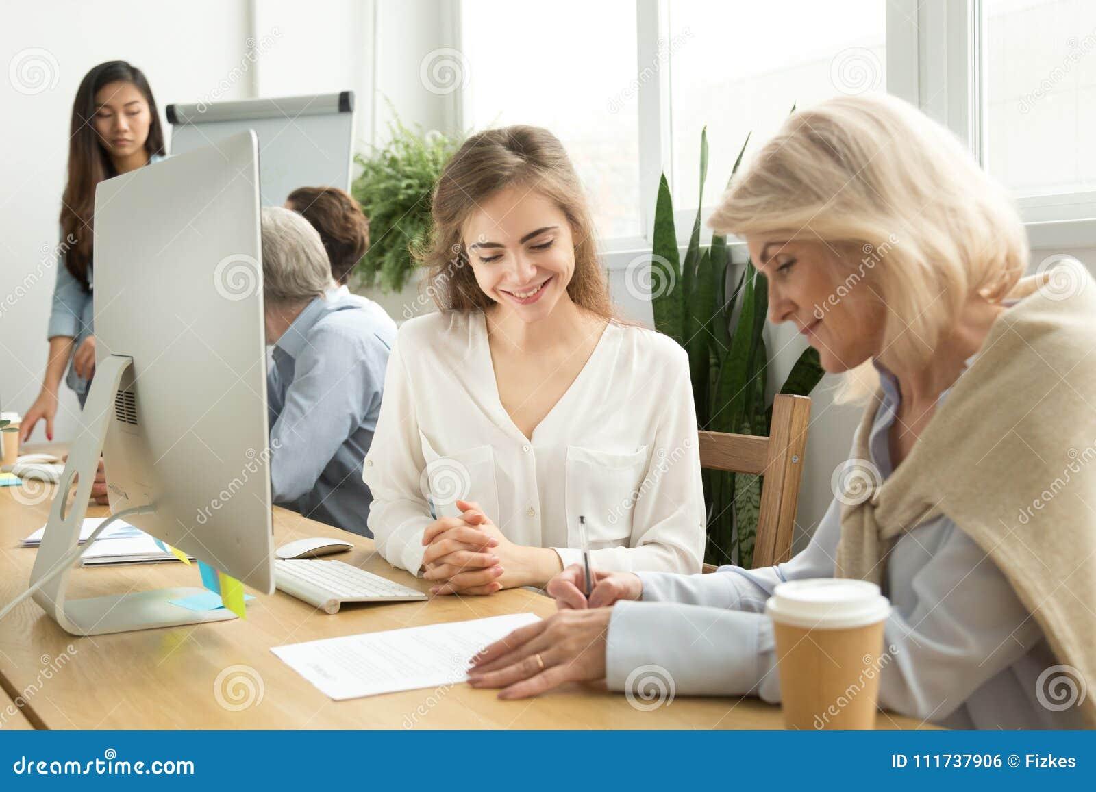 Contratto di firma della donna di affari più anziana con il responsabile femminile sorridente