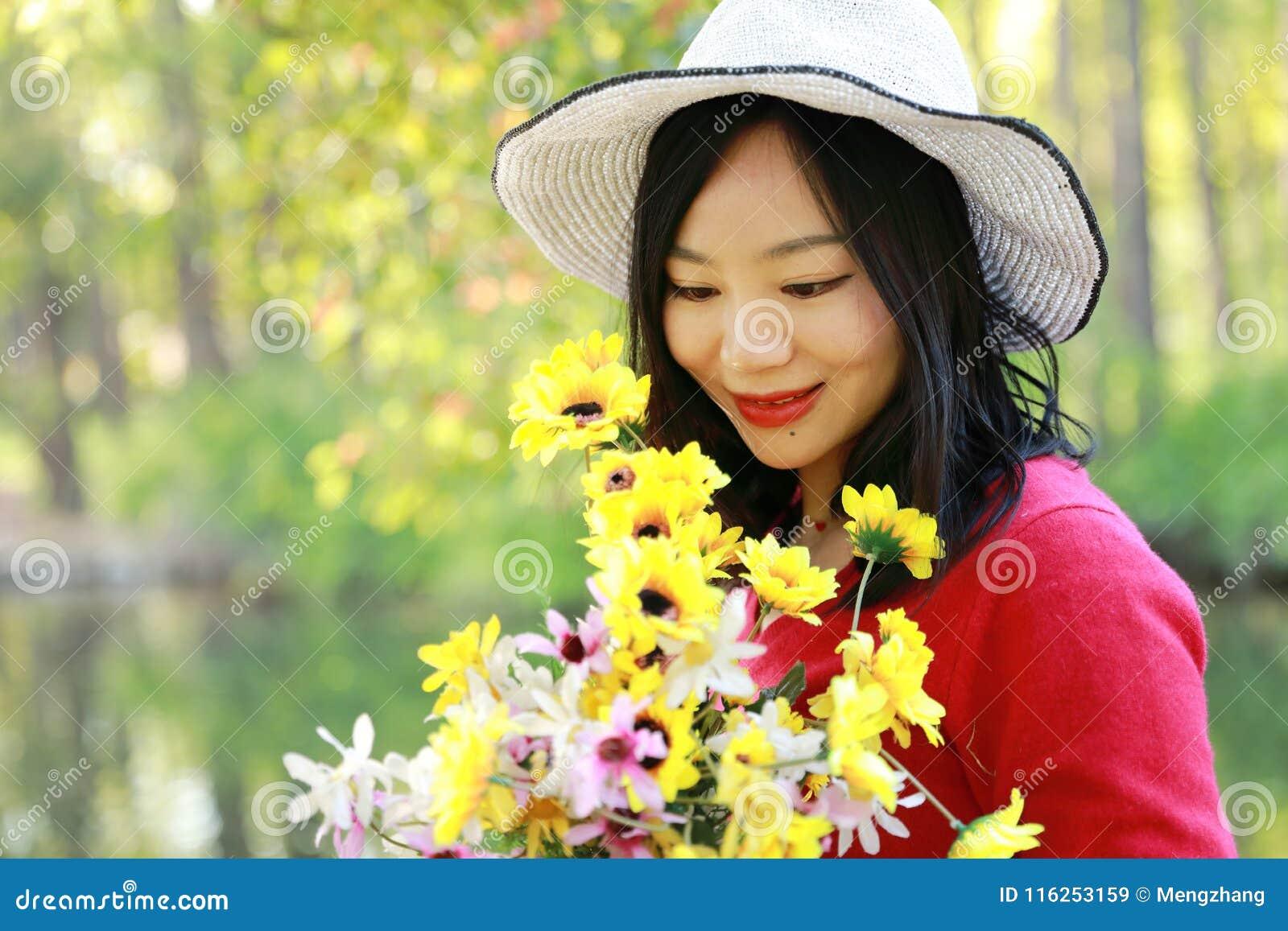 Control chino asiático feliz de la sonrisa de la muchacha de la belleza de la mujer que un manojo de paseo de la flor por el lago