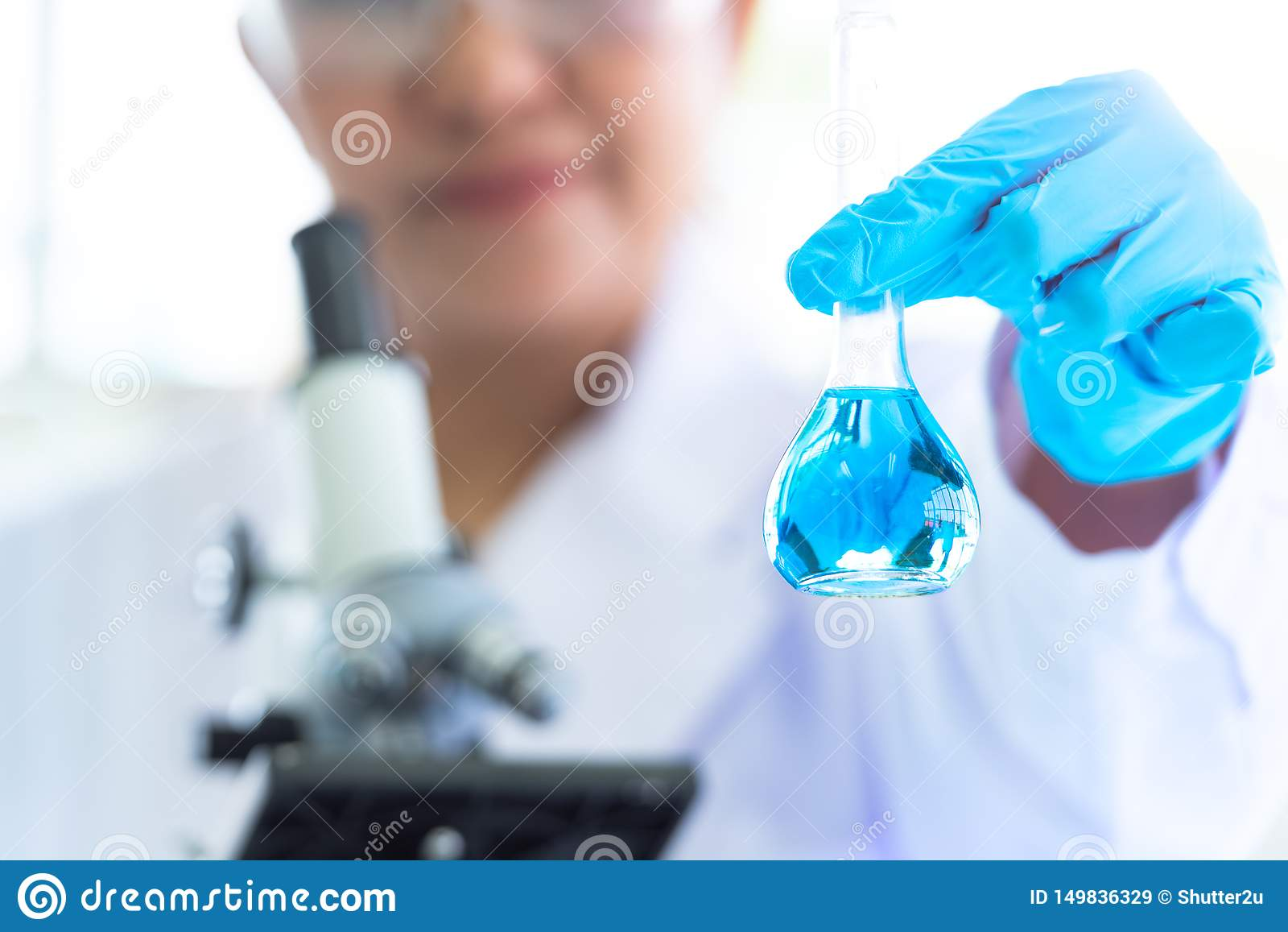Control femenino del científico y mostrar los tubos de ensayo y la solución del laboratorio con el estetoscopio Ciencia y fondo m
