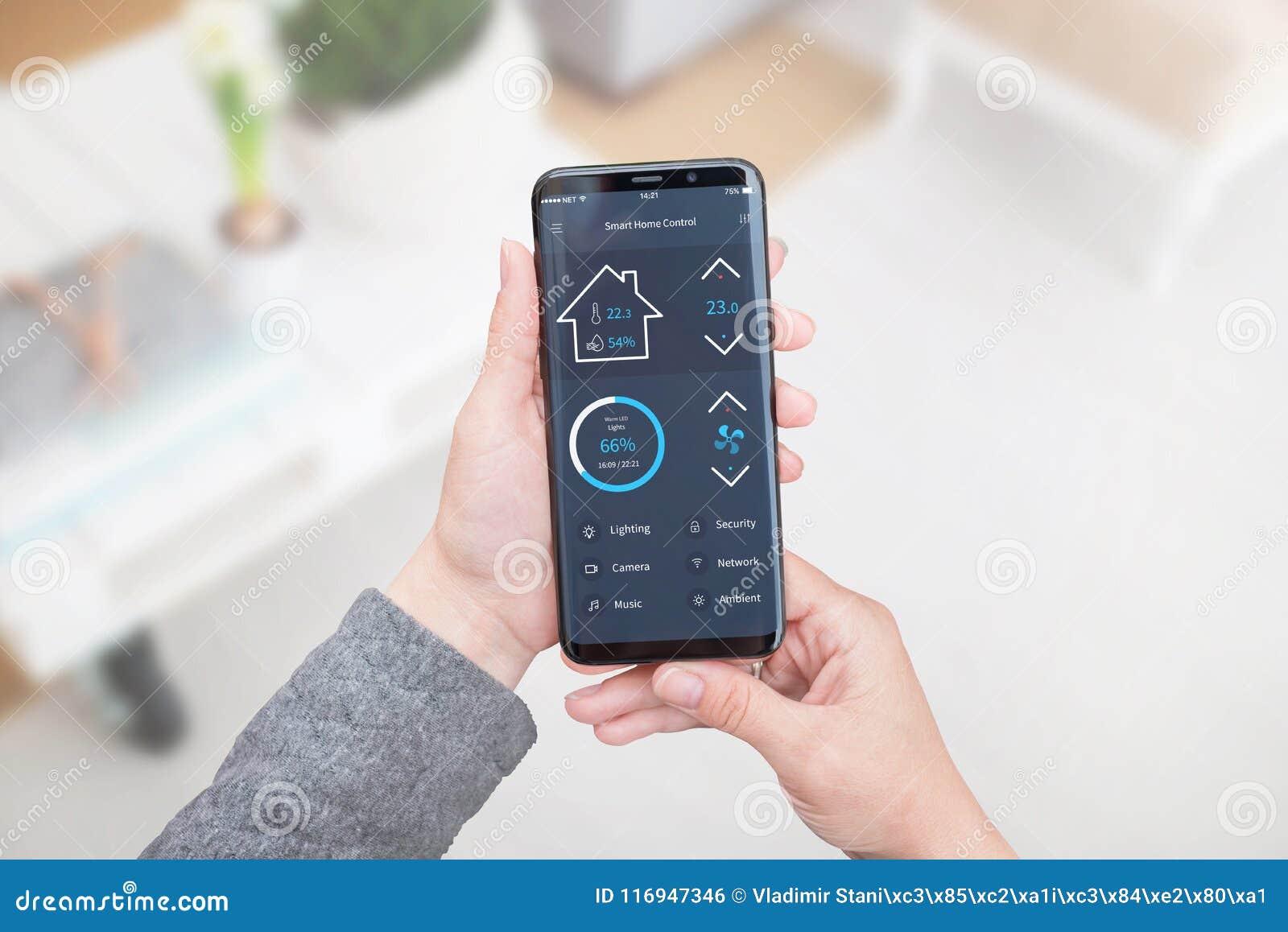 Controle home esperto app para dispositivos móveis na mão da mulher Interior da sala de visitas no fundo