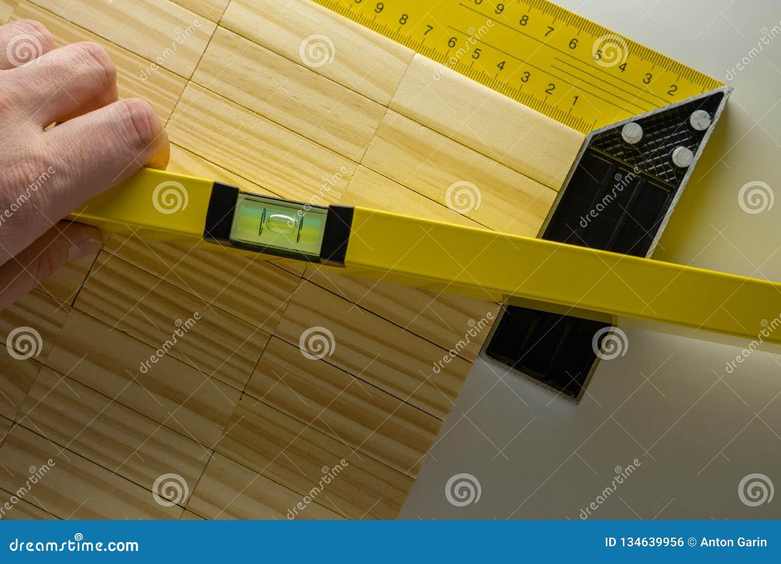 Controlerend het niveau van de lijst, hand met de bouw van niveau of waterpas en houten blokkenlijst