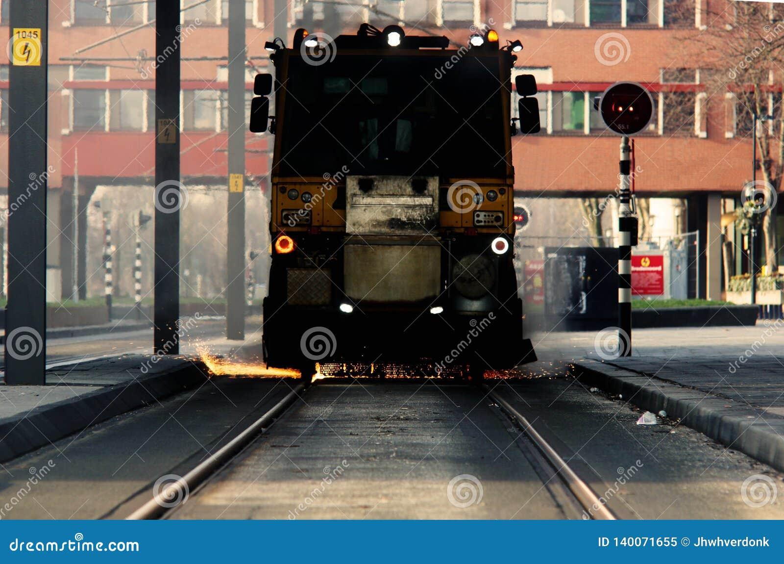Contruction arbete på en spårvagnlinje ser som spårvagnen derailing med många gnistor, brand som kommer från botten