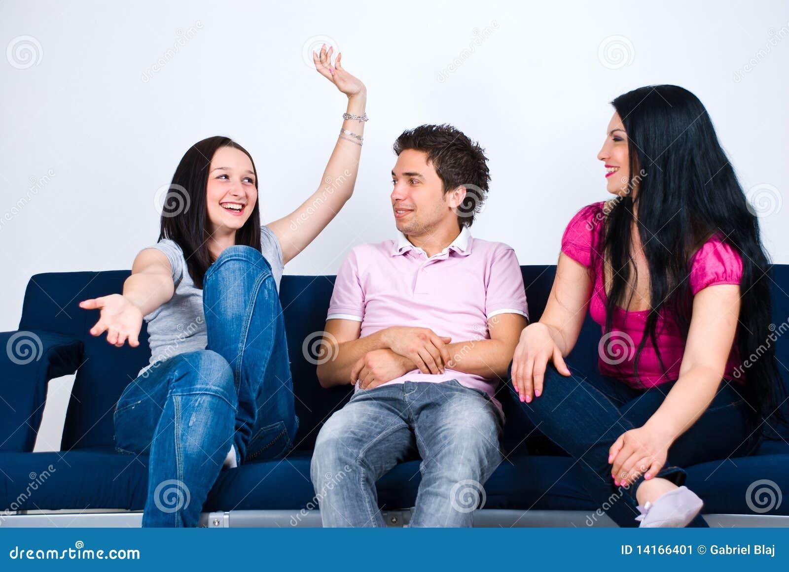 Conversação feliz dos amigos no sofá