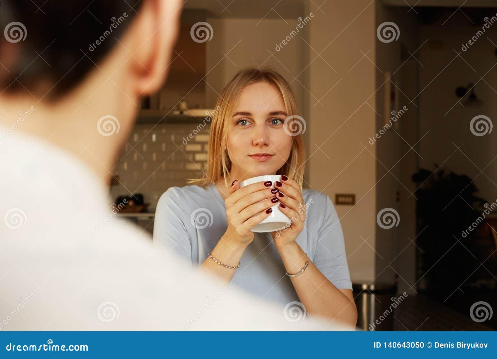 Conversación del hombre confiado y de la mujer rubia joven en casa