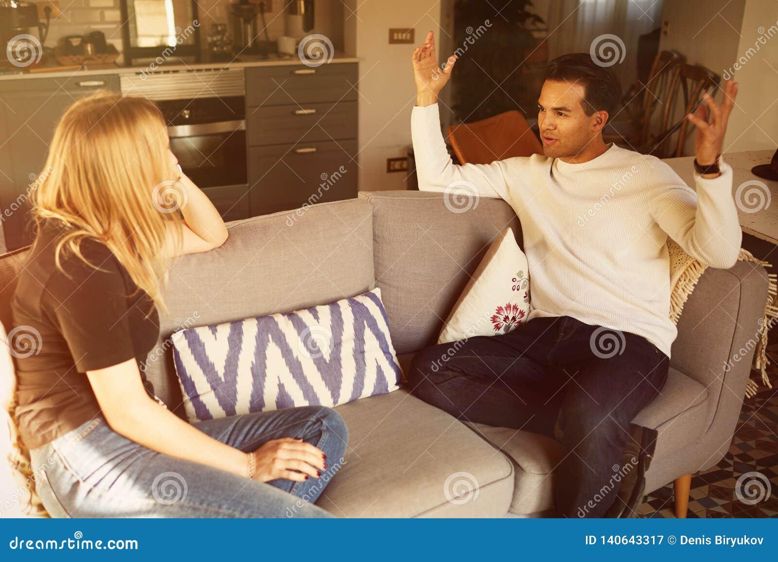 Conversation sur le sofa de l homme sûr et du jeune appartement blond de femme à la maison