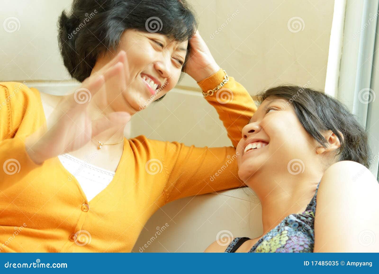 Conversazione felice della madre asiatica con la figlia teenager