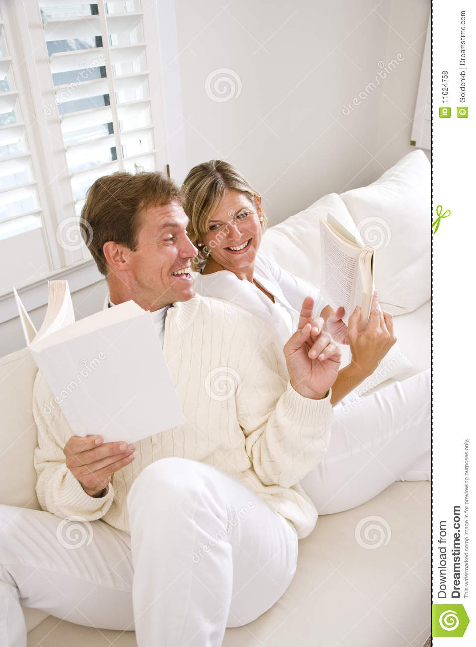 Conversing couple reading sofa together