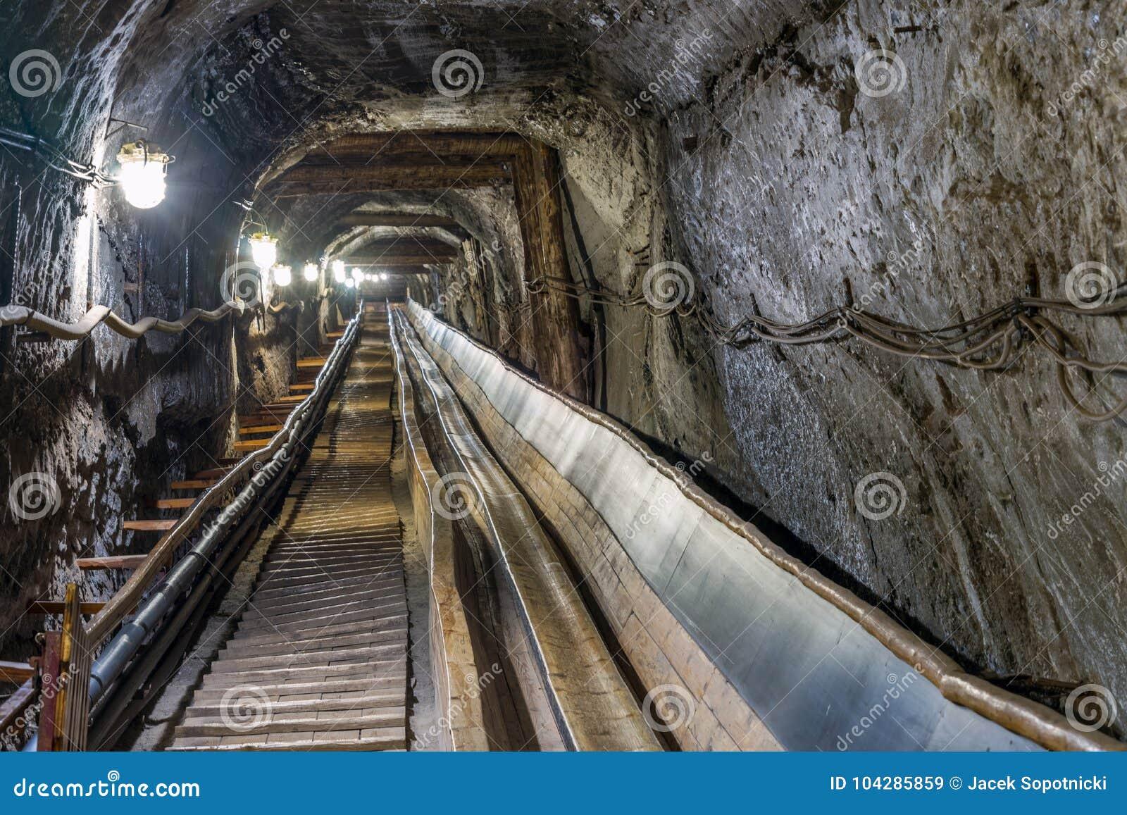 Conveyot da correia no túnel subterrâneo iluminado