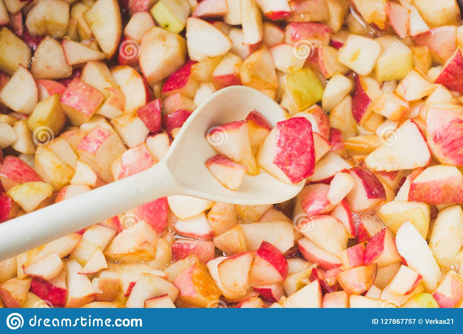 Cook apple jam and stir with a white plastic spoon. process of m