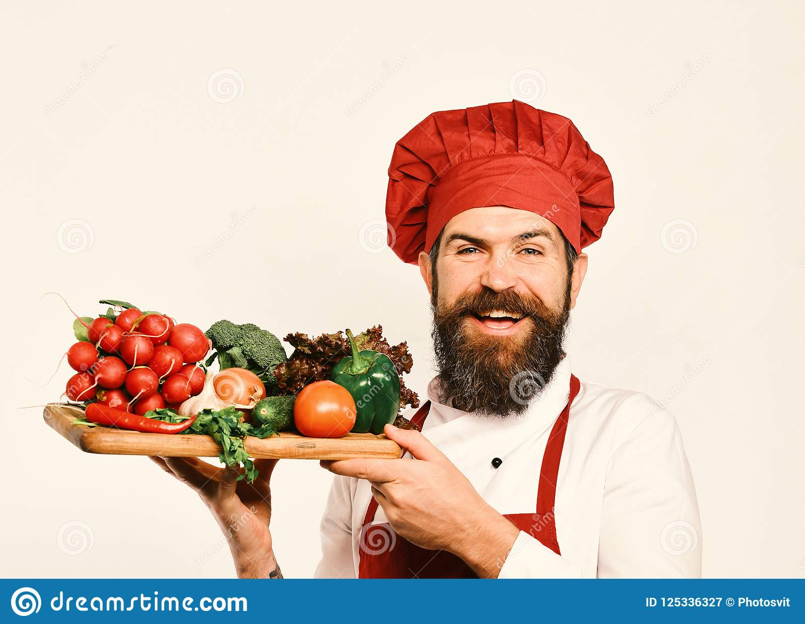 Cook with cheerful face in burgundy uniform holds salad ingredients. Chef holds board with fresh vegetables. Cooking and
