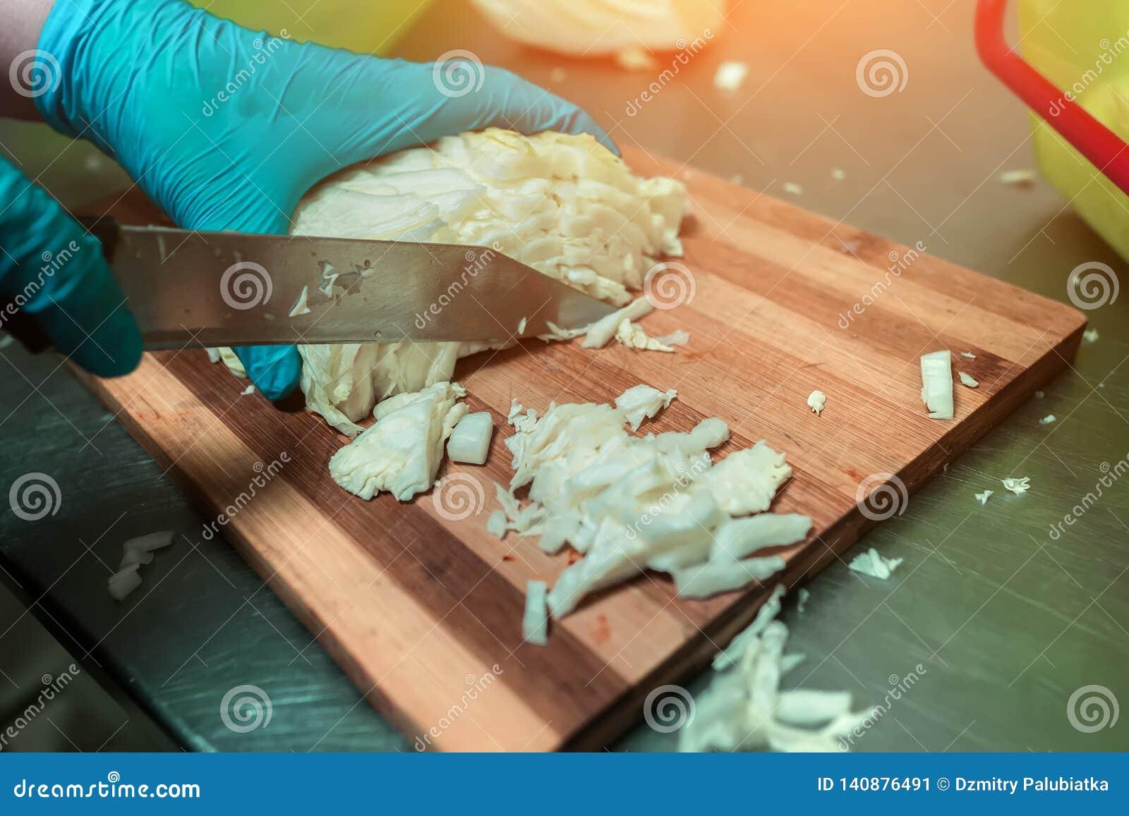 Cook cuts cabbage close-up