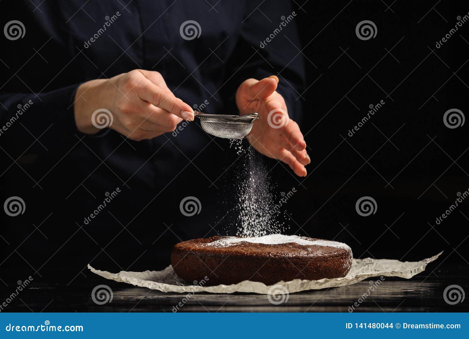 Cook kropi lodowacenie cukier na czekoladowym torcie
