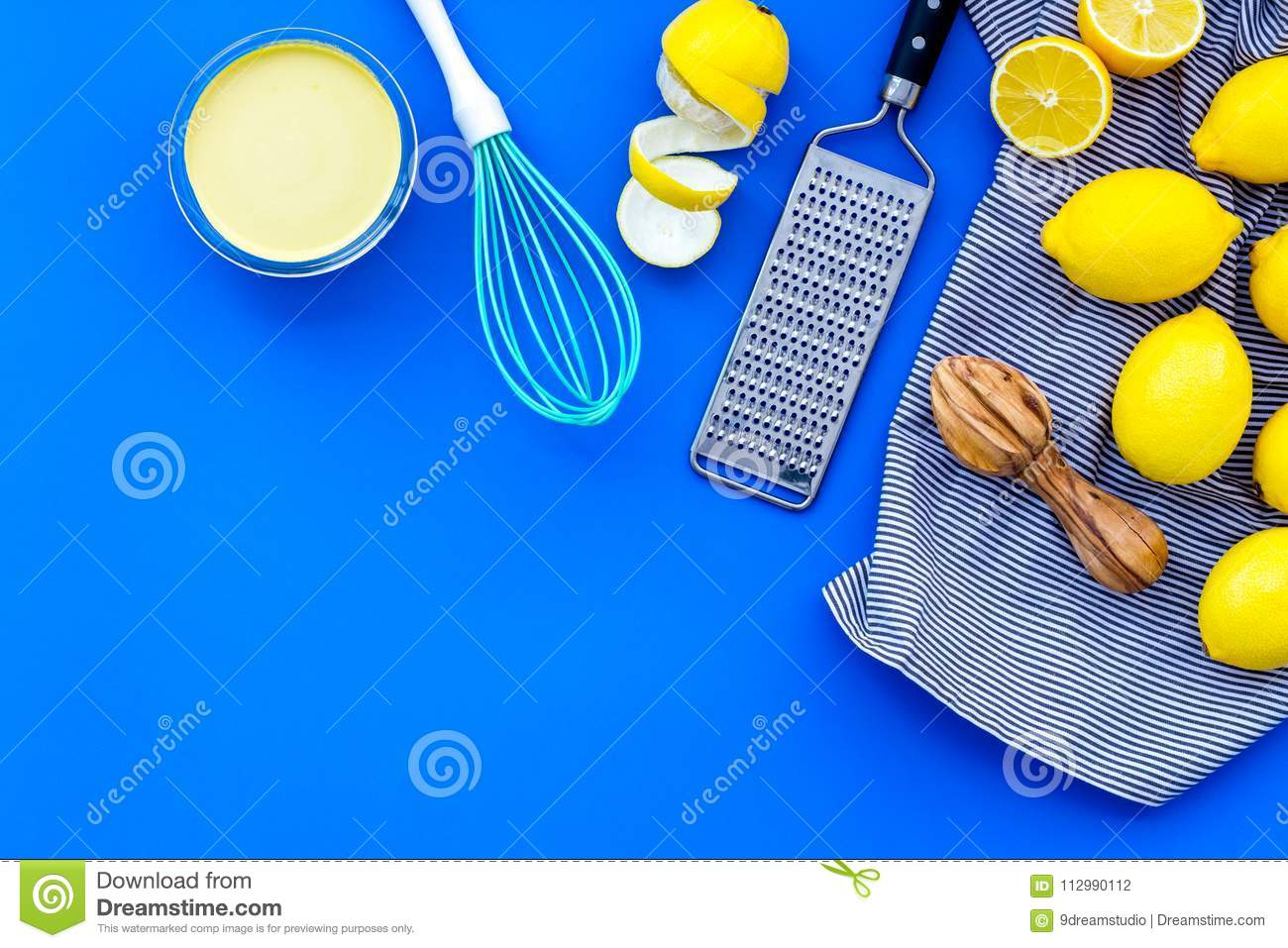 Cook lemon curd. Sweet cream in bowl, fruits, kitchen utensils on blue background top view copy space