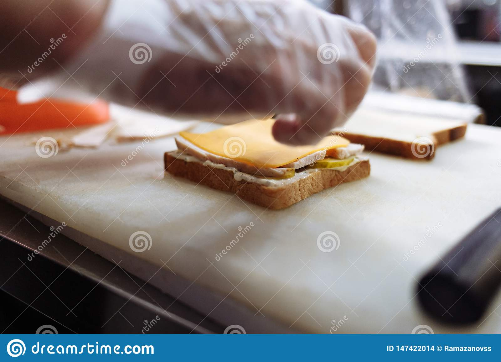 Cook in polyethylene gloves making a sandwich on a white board