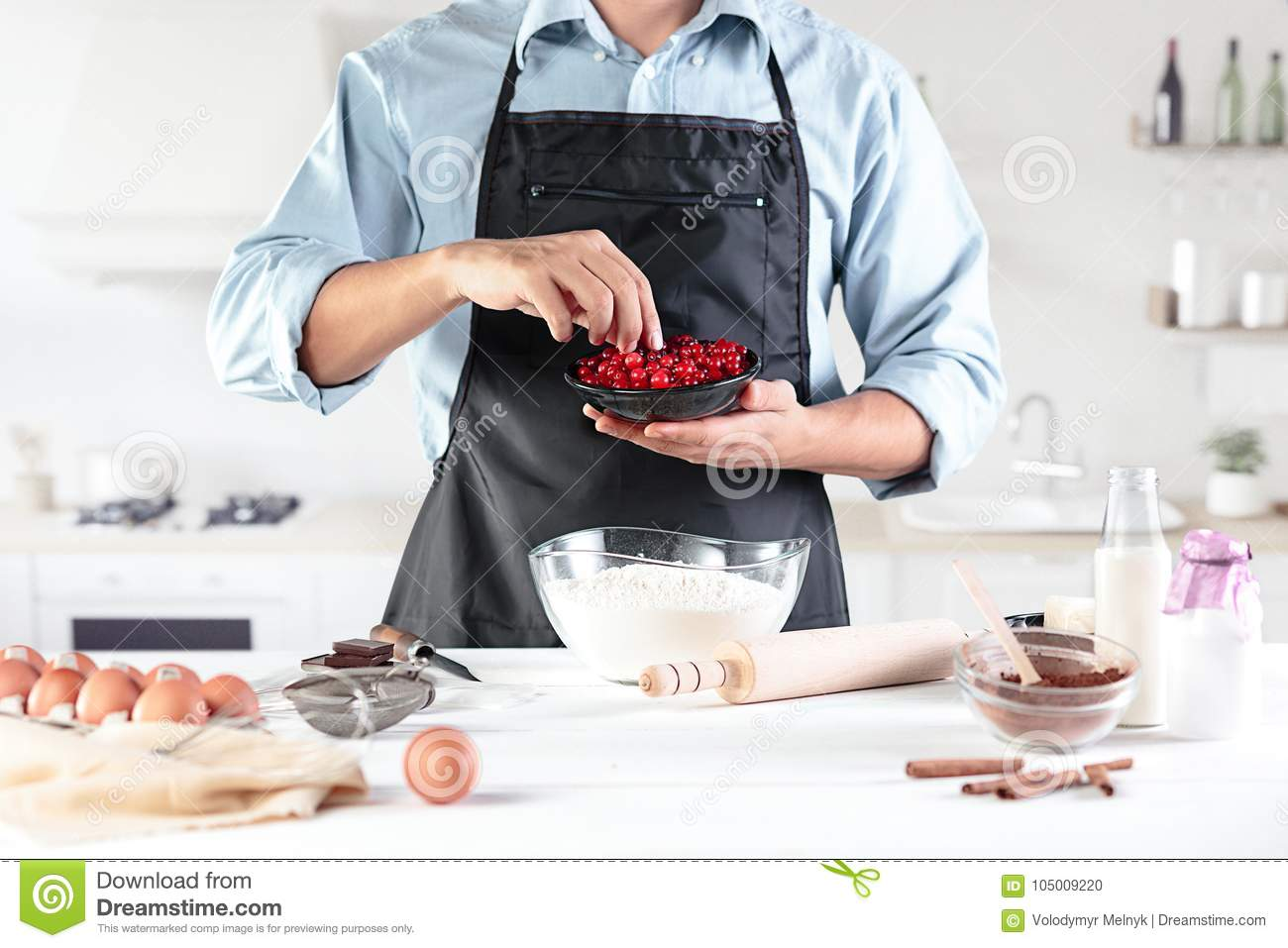 A cook with eggs on a rustic kitchen against the background of men`s hands