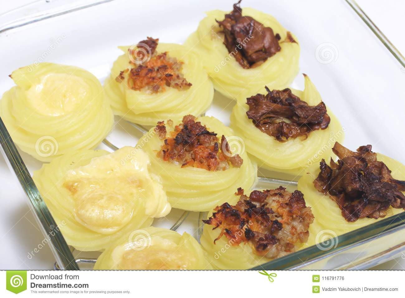 Cooked potato croquettes stuffed with cheese, mushrooms and minced meat. They lay in a glass baking sheet. The ingredients are on