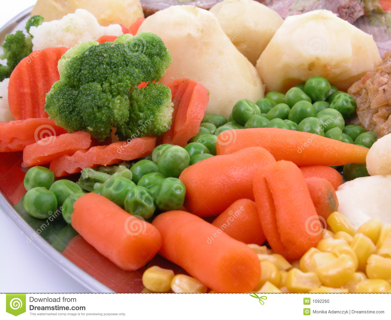 Cooked potatoes carrots sweet pea corn and broccoli on plate.