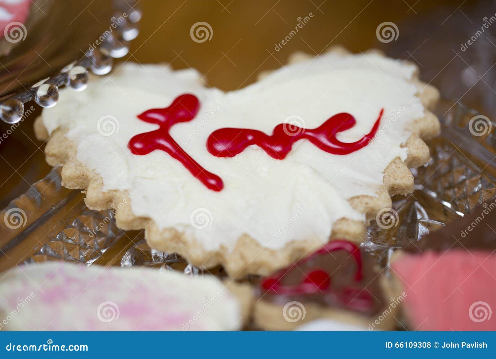 Cookie do coração do Valentim com o amor da palavra escrito no frostin vermelho