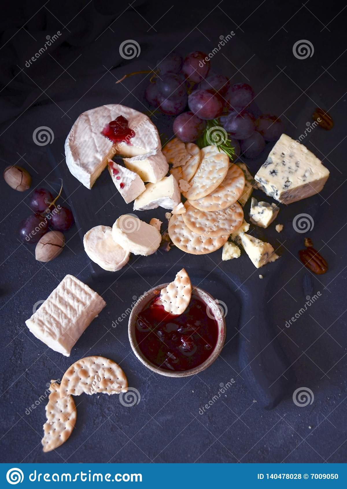 Cookies with cheese nuts jam and grapes