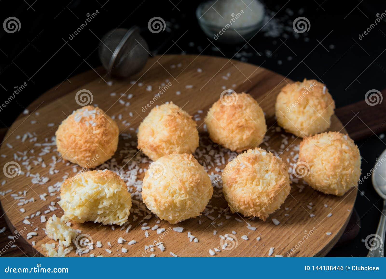 Cookies crocantes Congolais do coco em uma placa de madeira contra um fundo escuro