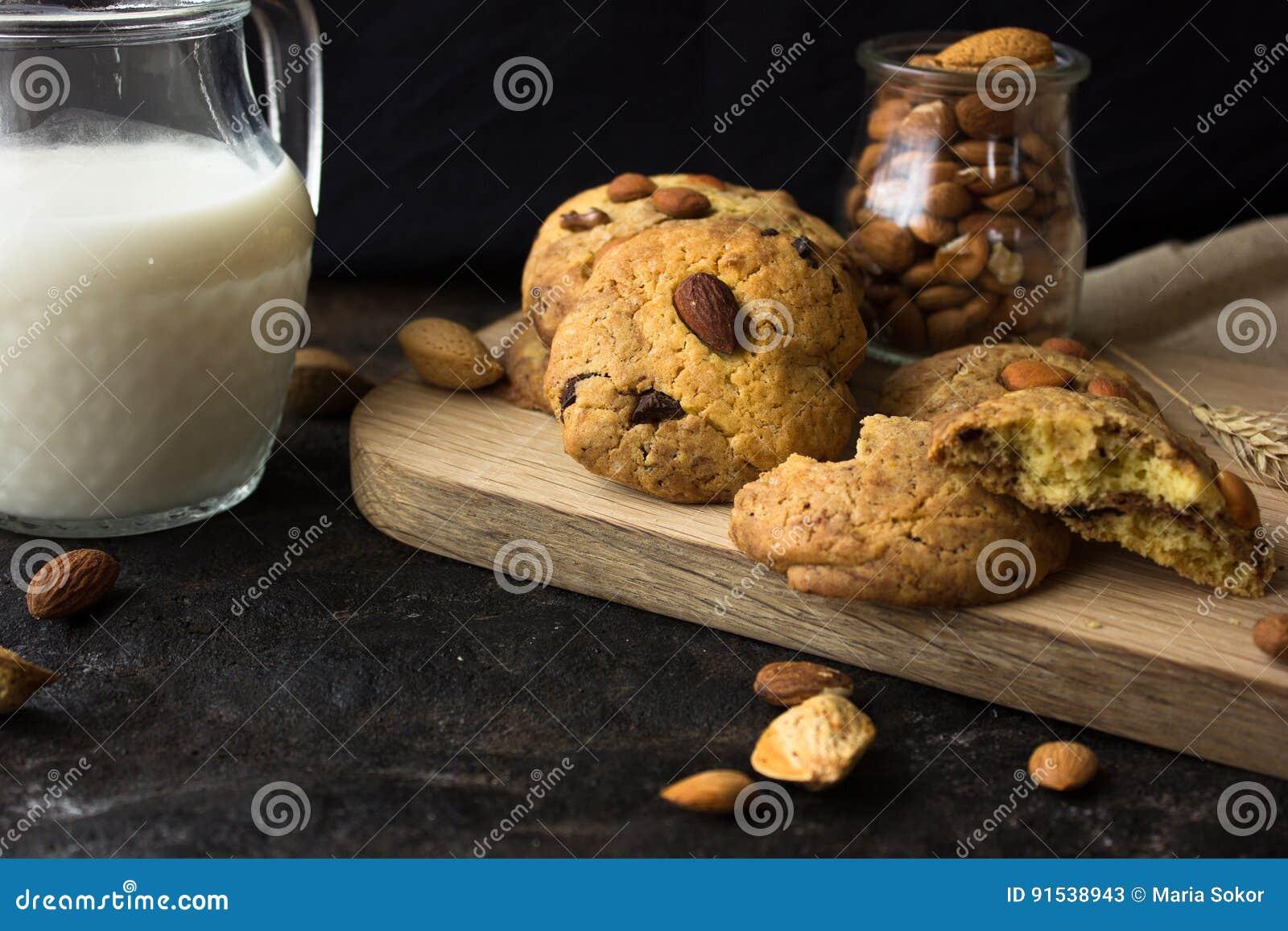Cookies de biscoito amanteigado americanas com gotas de chocolate e um jarro de leite e de amêndoas Fundo escuro do grunge Luz mí